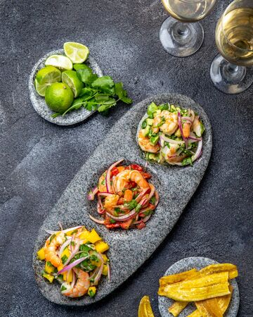 CEVICHE. Three colorful shrimps ceviche with mango, avocado and tomatoes. Latin American Mexican Peruvian Ecuadorian food. Served with white wine and banana chips