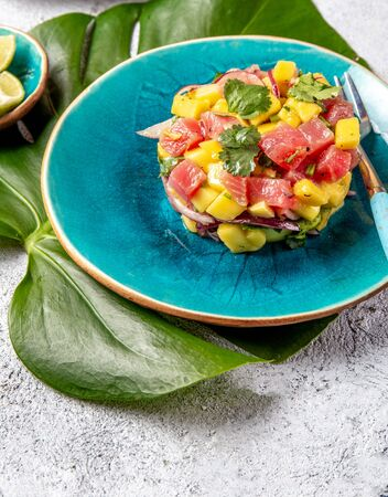 Tropical style gourmet tuna mango salad tartar with cilantro and purple onion. On blue plate, tropical leaves