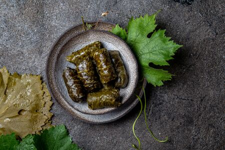 Traditional Middle Eastern dolma or tolma. Grape leaves stuffed with meat and rice. On Gray plate, gray concrete background. Zdjęcie Seryjne