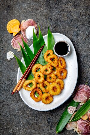 Fried squids rings on white plate decorated with tropical leaves, gray concrete background, top view Zdjęcie Seryjne
