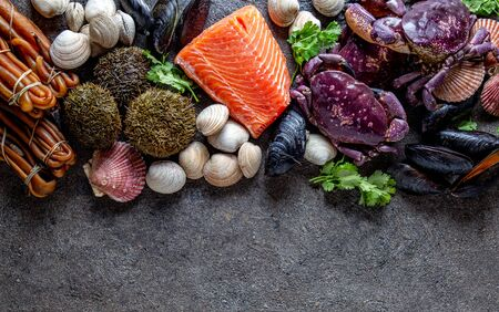 PACIFIC SEAFOOD. Fresh salmon, crabs ostions clams mussels, seaweed cochayuyo, sea urchins. Food background with copy space. Imagens