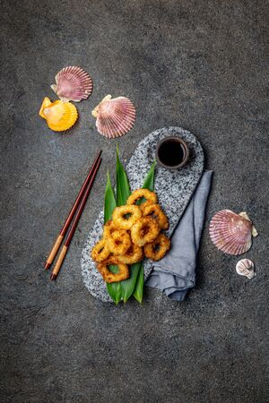 Fried squid rings on stone plate decorated with tropical leaves. Asian food concept. Top view 스톡 콘텐츠
