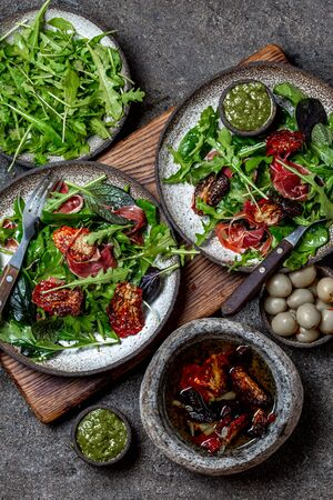 Salad with arugula, spinach, dried tomato and ham serrano paleta iberica. Low carbs keto recipe.