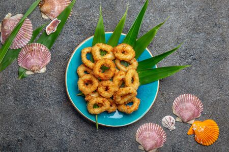 Fried squids rings on blue plate decorated with tropical leaves. Gray concrete background and sea decoration. Top view Stock Photo