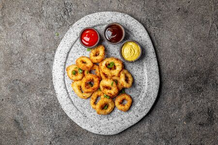Fried squids rings on gray stone plate with sauces. Gray concrete background. Zdjęcie Seryjne