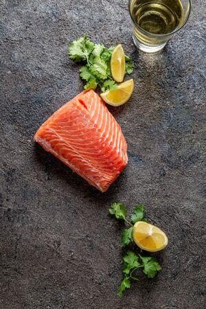 Food background with fresh salmon filet steak, lemon and coriander.