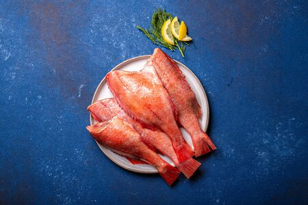 Fresh red sea bass on blue background. Top view, copy space.