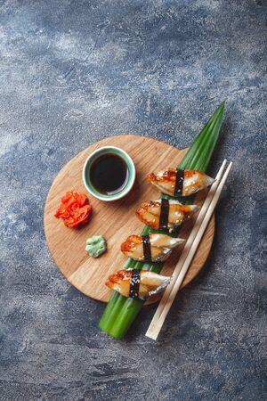 Sashimi sushi set on wooden board. Stone background. Top view.