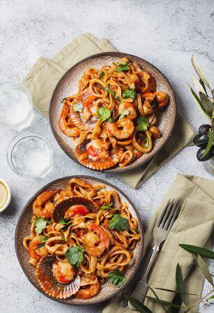 Seafood Spaghetti with seashells, prawns, squids on gray background. Italian mediterranean food concept.