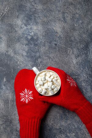 Christmas and New Year cozy holiday composition with scarf, woman hands in mittens, mugs with hot drink and marshmallow on the gray concrete background. Flat lay, top view Stock Photo