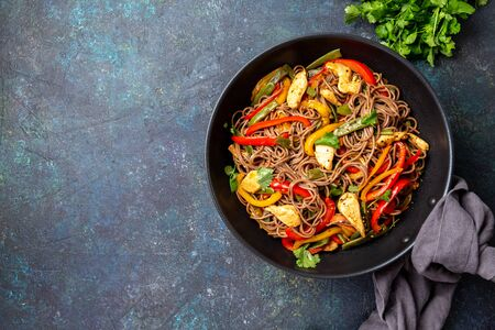 Japanese dish buckwheat soba noodles with chicken and vegetables carrot, bell pepper and green beans in wok on dark blue background.