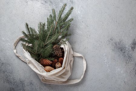 Zero waste Christmas concept. Natural Chirsmas decoration, pine cones and branches in linen bag. Flat lay, top view