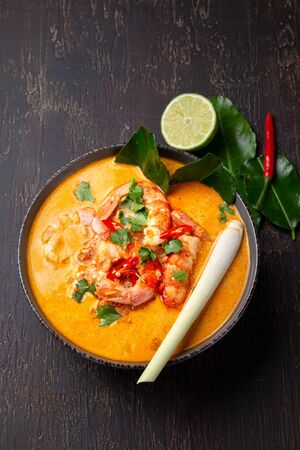Shrimps Tom Yam Kung in grey bowl with thai spices on autentic tray top view, wooden background Zdjęcie Seryjne