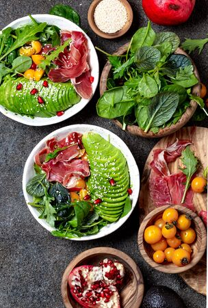 Low carbs bowl. Fresh salad with green spinach, rucola, avocado an ham serrano in white bowl, gray background, top view. Zdjęcie Seryjne