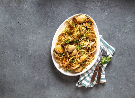 Seafood Pasta. ITALIAN SPAGHETTI ALLE VONGOLE. Clams spaghetti on white plate with white wine, gray background. Top view.