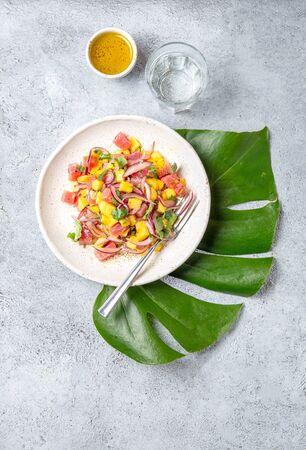 Tropical Hawaiian tahitian tuna mango salad on white plate on tropical monstera leafe.