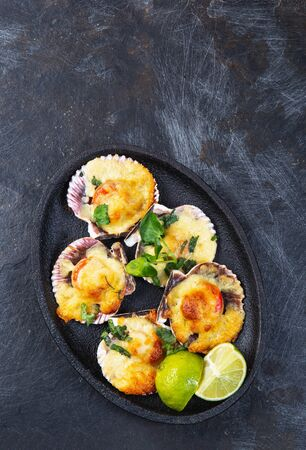 Baked seafood shellfish scallops with cheese and lemon. black background.