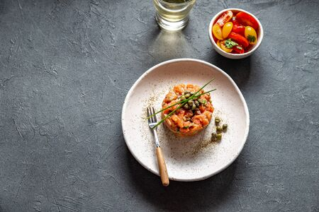 SALMON TARTAR with capers and purple onion on white plate, gray background. Stock fotó
