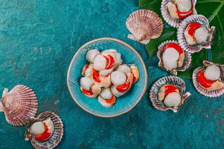 Raw fresh seafood shellfish scallops on blue background. 版權商用圖片