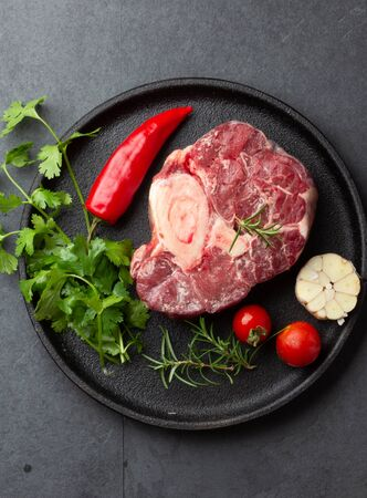 Raw fresh ossobuco con herbs, garlic and chile pepper on black plate. Dark background. 스톡 콘텐츠