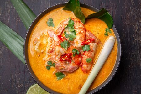 Shrimps Tom Yam Kung in grey bowl with thai spices on autentic tray top view, wooden background.