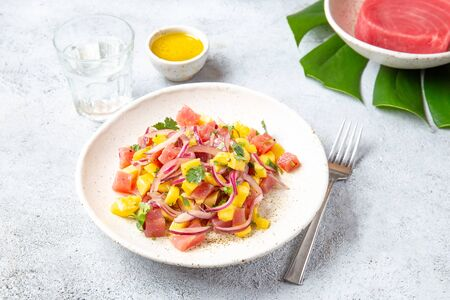 Tropical Hawaiian tahitian tuna mango salad on white plate on tropical monstera leafe.