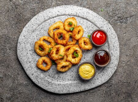 Fried squid rings on gray stone plate with sauces. Gray concrete background