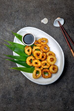 Fried squid rings on white plate decorated with tropical leaves. Gray concrete background, top view