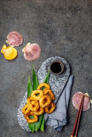 Fried squid rings on stone plate decorated with tropical leaves. Asian food concept, soy sauce and chopsticks
