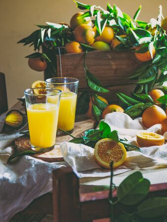 Table with box of fresh orange with orange tree branch and fresh orange juice. Reklamní fotografie