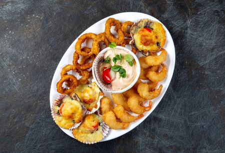 PERUVIAN FOOD. Piqueo caliente. Hot seafood platter fried shrimps, squid rings and baked scallops with sauce.