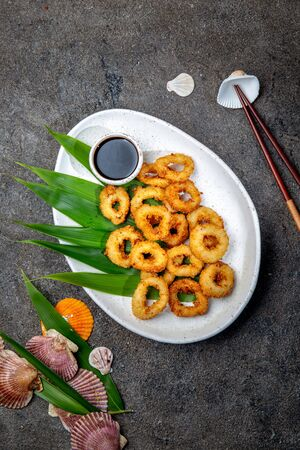 Fried squids rings on white plate decorated with tropical leaves, gray concrete background, top view Stock Photo