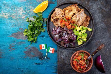 Yucatan Mexican Food Pork POC CHUC poc chuck. Pork marinaded in orange juice served with avocado, purple onion and rustic tomato sauce Archivio Fotografico
