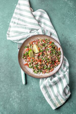 Traditional Lebanese salad tabouli tabule with quinoa, herbs, tomatoes, mint and lemon.