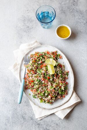 Quinoa Quinua salad with tomatoes and herbs in white bowl.