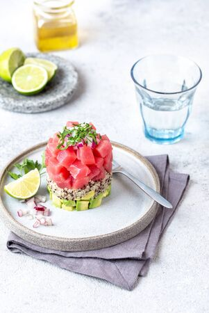 Tuna tartare tartar with avocado and quinoa. gourmet presentation with culinary ring on wite plate.