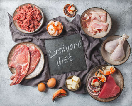 Carnivore diet concept. Raw ingredients for zero carb diet - fish, seafood, eggs, meat and animal fats. Top view or flat lay.