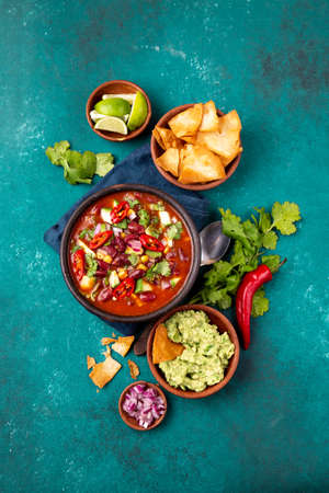 Mexican food concept background with chile black bean soup, guacamole and nachos totopos. Top view