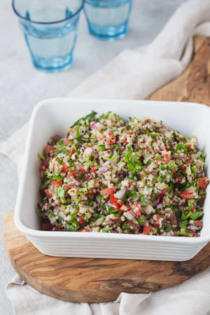 Quinoa Quinua salad with tomatoes and herbs in white bowl