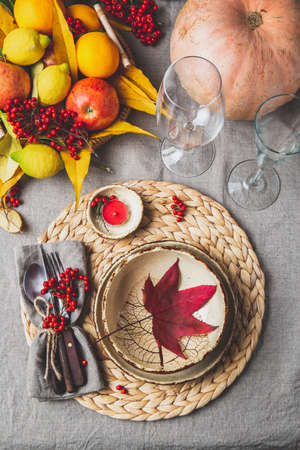 Autumn fall thankisgiving day table setting with pumpkins, fruits and yellow leaves, autumn decoration.