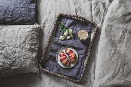 Breakfast tray on a bed. Croissant and coffee on bamboo tray on linen bedclothes