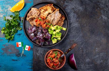 Yucatan Mexican Food Pork POC CHUC poc chuck. Pork marinaded in orange juice served with avocado, purple onion and rustic tomato sauce. Archivio Fotografico