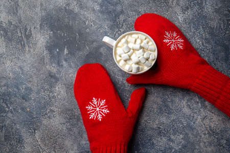 Christmas and New Year cozy holiday composition with scarf, woman hands in mittens, mugs with hot drink and marshmallow on the gray concrete background. Flat lay, top view. Imagens - 155707425