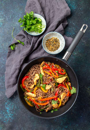 Japanese dish buckwheat soba noodles with chicken and vegetables carrot, bell pepper and green beans in wok on dark blue background