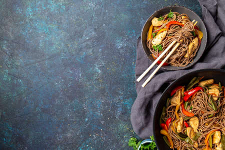 Japanese dish buckwheat soba noodles with chicken and vegetables carrot, bell pepper and green beans in grey bowl, top view, copy space Imagens