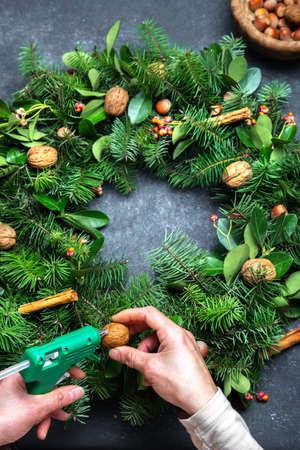 Women making Christmas wreath. New year holidaydecoration