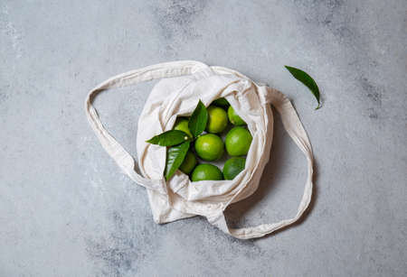 Ripe limes with fresh lime tree leaves in eco linen bag. top view Imagens