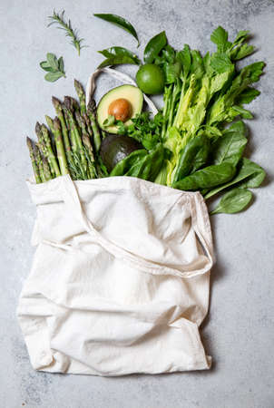 Healthy food ingredients green vegetables and fruits in eco linen bag, zero waste and clean eating concept. gray background