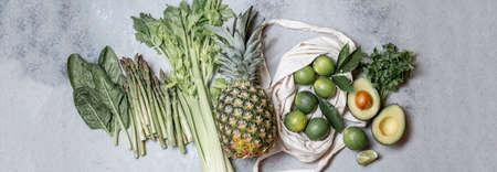 Healthy food ingredients gree vegetables and fruits on gray background