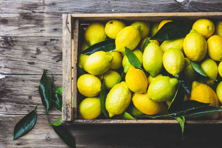 Full box of fresh lemons. Top view, copy space